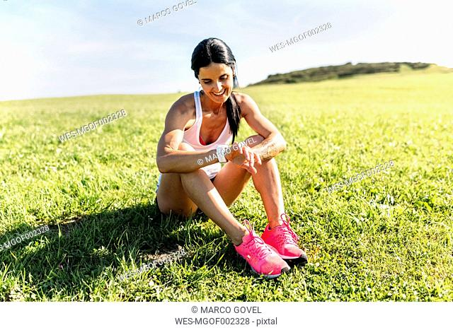 Woman sitting on grass, checking heart rate monitor