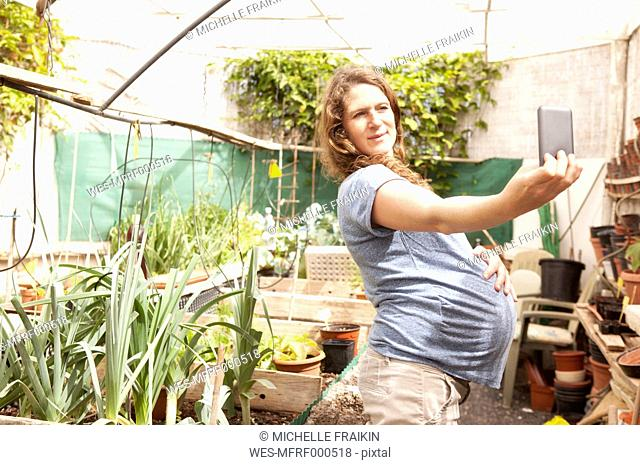 Pregnant woman taking a selfie in greenhouse