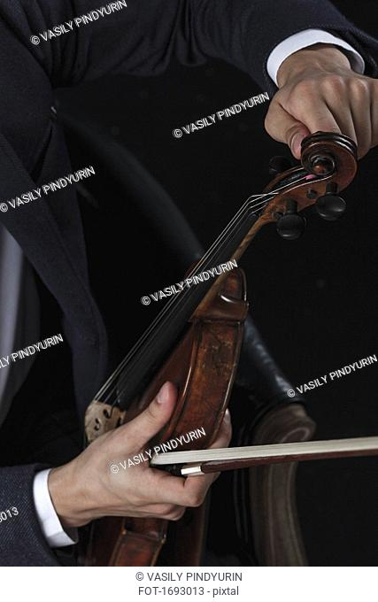 Cropped image of violinist tuning violin while sitting on chair