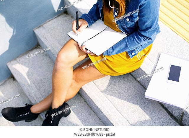 Young woman sitting on steps writing down something, partial view
