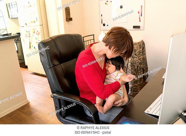 Mother cradling sleeping baby at work desk