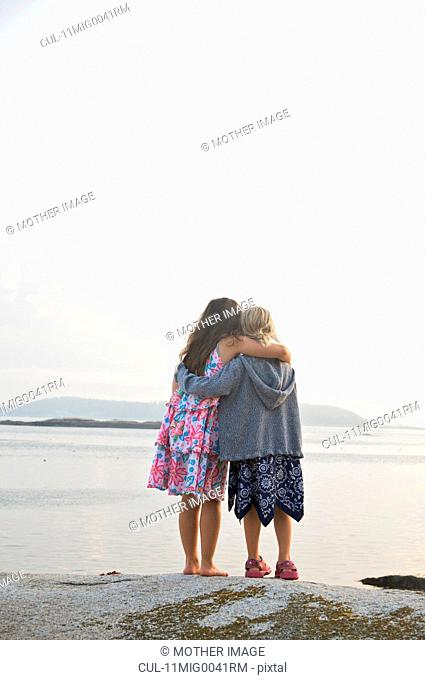 Two girls arm in arm by coastline