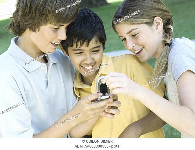 Three preteen friends looking at cell phone