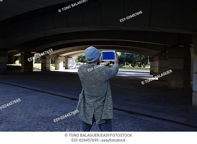 Modern young man with tablet pc touch taking photos under a bridge with wool cap