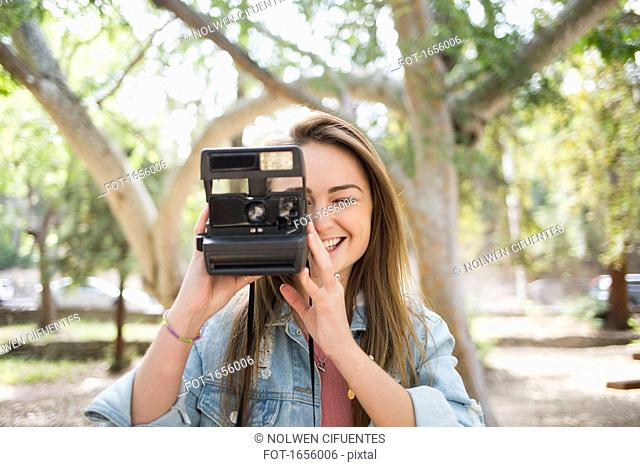 Happy young woman using instant camera at park