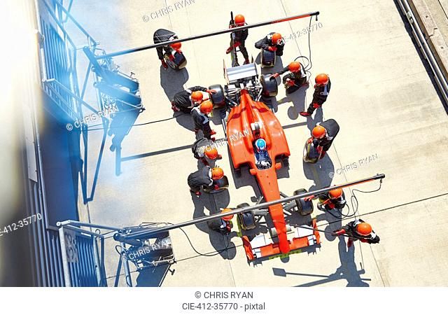 Overhead pit crew replacing tires on formula one race car in pit lane