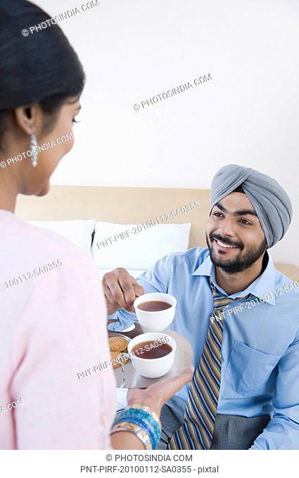 Woman serving tea to her husband
