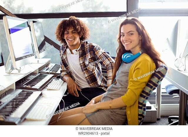 Portrait of male and female sound engineer sitting in office