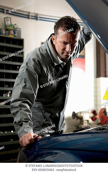 Smiling mechanic controlling car engine