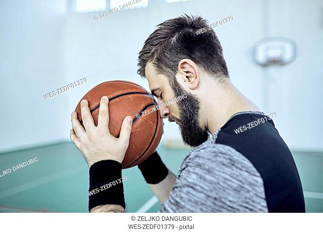 Man with basketball, closed eyes, indoor