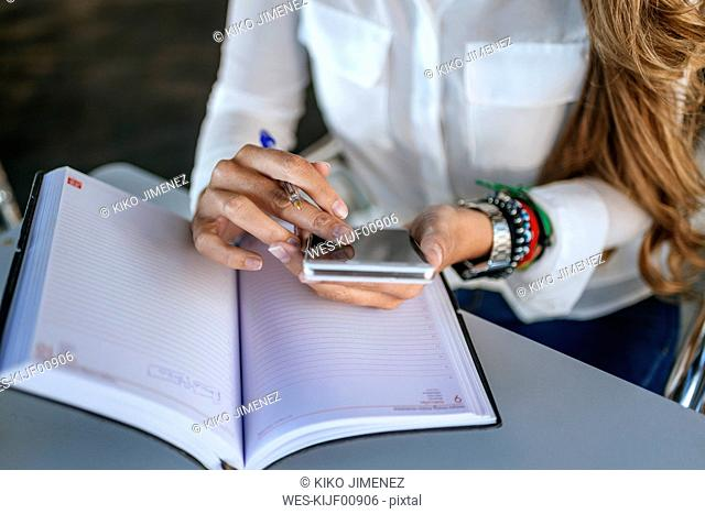 Close-up of woman's hands using a smartphone and a notebook