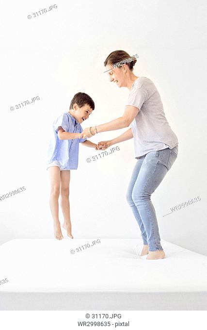 Smiling woman and boy holding hands, jumping on a bed