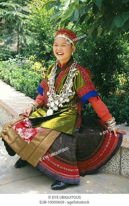 Seated Miao girl wearing festival dress