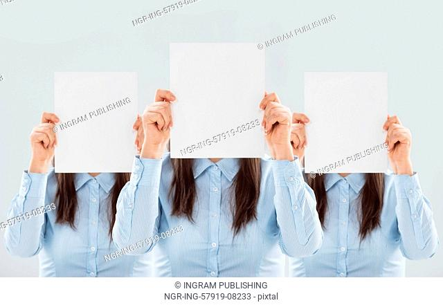 Three women showing blank paper sheets in front of their heads