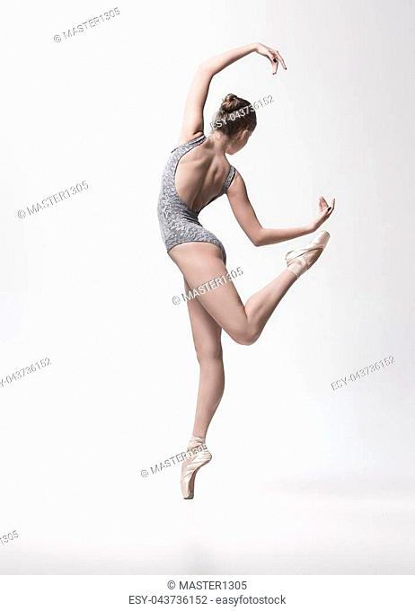 Young classical dancer dancing on white background. Ballerina project