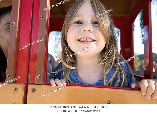 face of four years old blonde girl leaning out the window of playground house in public park, next to mother