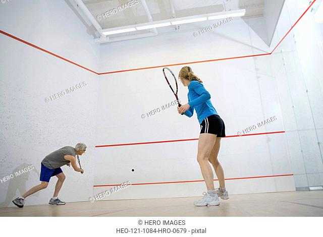 Couple playing squash on court