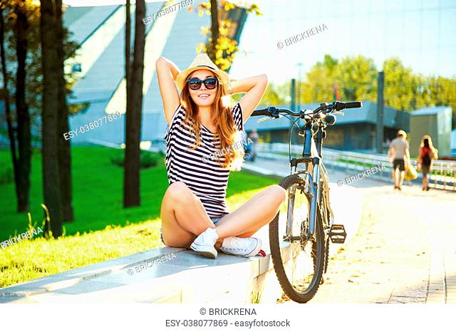 Happy Hipster Teenage Girl with Her Bike Relaxing in the City. Hands behind Head. Warm Toned Photo with Copy Space. Urban Youth Lifestyle Concept