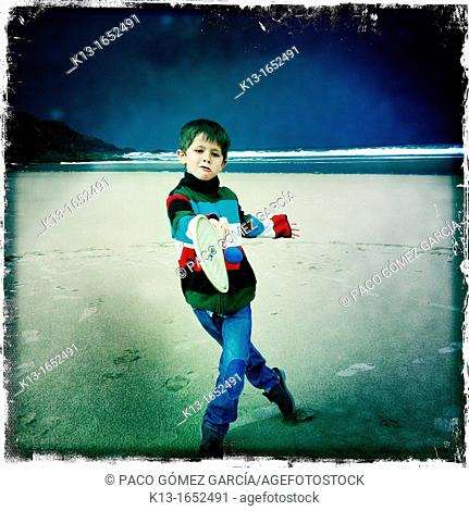 Boy playing tennis in Odeceixe beach in Alentejo, Portugal