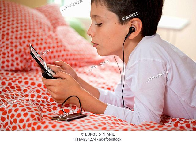 10 years old boy playing with video game console