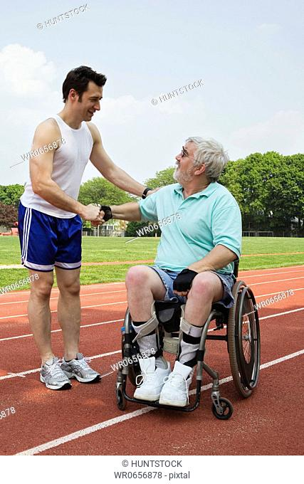 Handicapped senior man shaking hand with a young man