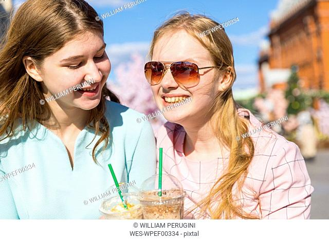 Russia, Moscow, teenage girls drinking a delicious frappe in the city