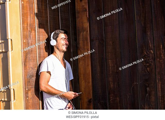 Happy young man with cell phone and headphones leaning against wooden wall