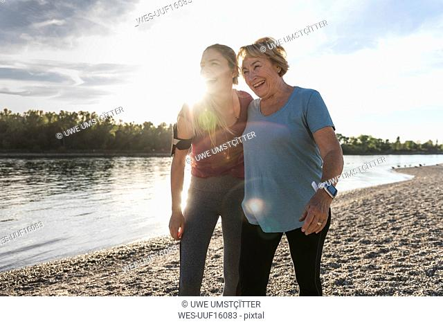 Fit grandmother and granddaughter walking at the river with arms around, having fun