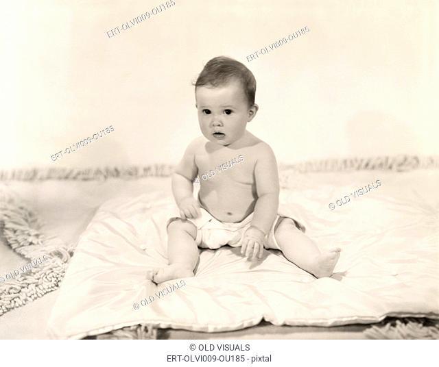 Portrait of baby girl sitting on blanket