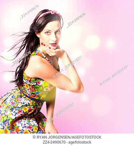 Feminine pink styled photograph of a beauty girl with long blowing brunette hairstyle interlaced with abstract bokeh light blurs. Hair style pin up