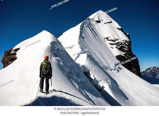 Climber arriving Pequeño Alpamayo summit. Cordillera Real range, Andes. Bolivia. South America