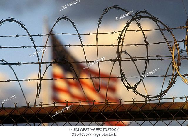 Detroit, Michigan - The American flag flies over a warehouse protected with razor wire