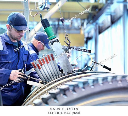 Engineers fitting blades to steam turbine in turbine repair works