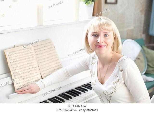 Young beautiful Caucasian woman sitting on a background of piano notes