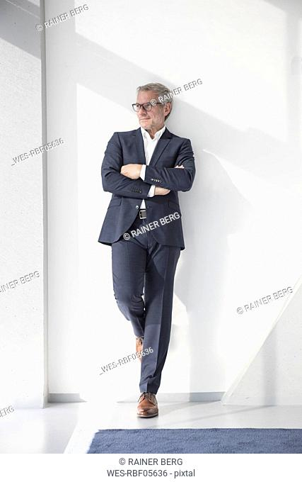 Confident businessman leaning against a wall