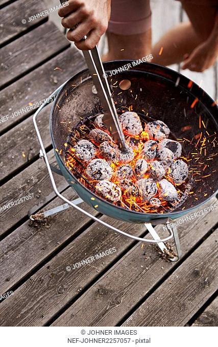 Preparing charcoal in grill