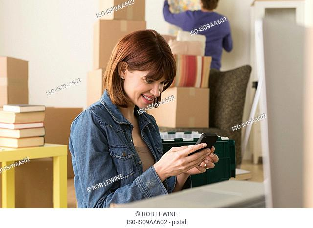 Woman looking at cellphone whilst moving house