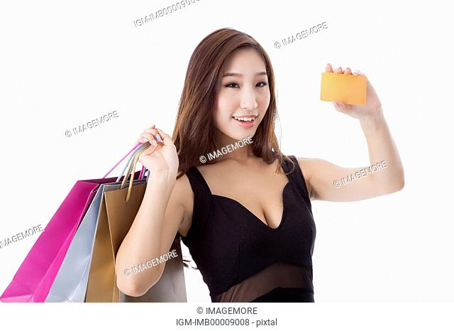 Young woman holding shopping bags and credit card with smile