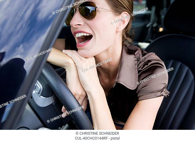 Smiling woman wearing sunglasses in car