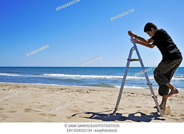 Boy (14) climbing a step ladder on beach, Camargue, France
