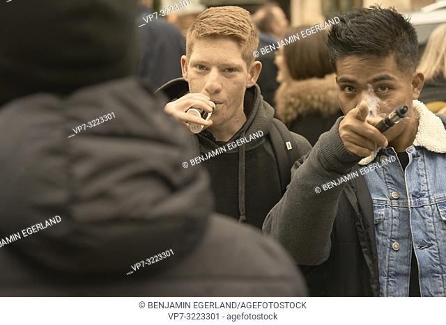 young men smoking electro cigarette, in Munich, Germany