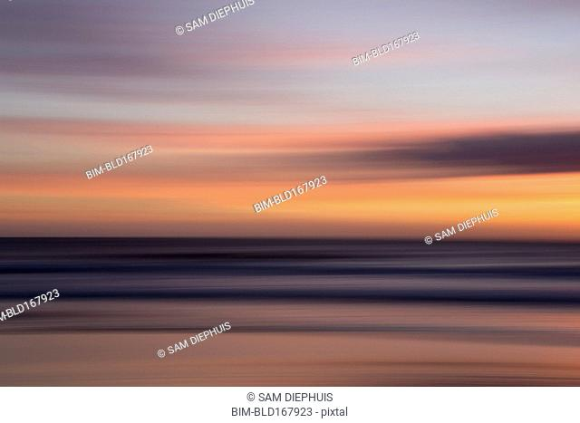 Defocused view of ocean waves on beach under sunset sky