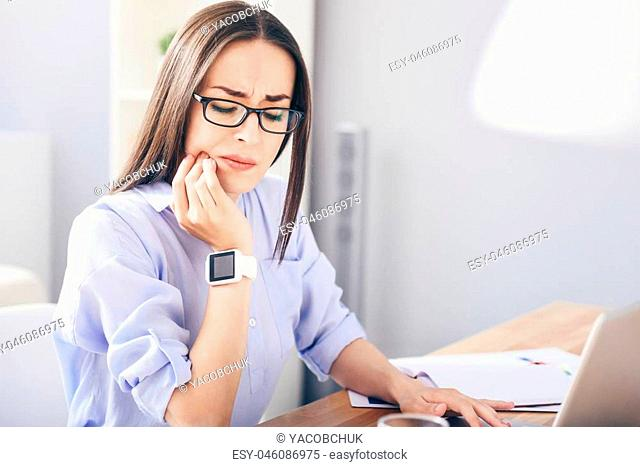 Can nor resist it. Serious young woman using laptop and suffering from toothache