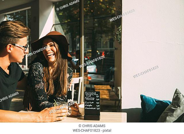 Couple sitting in a coffee shop having fun