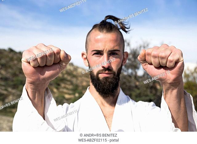 Portrait of man doing martial arts pose outdoors