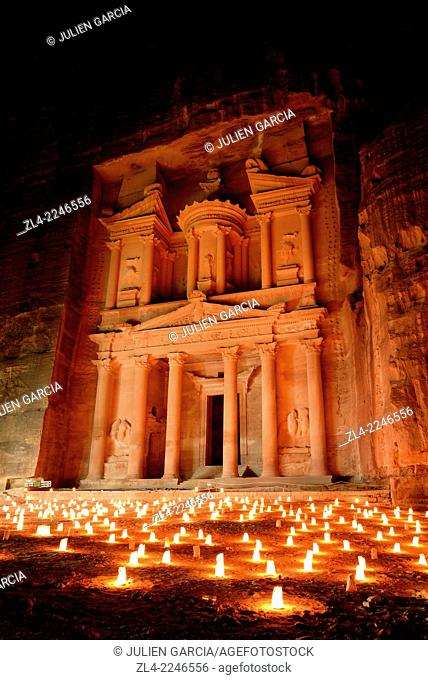 """The famous and elaborately carved façade of Al Khazneh (the Treasury), carved out of a sandstone rock face, lighted with candles during """"""""Petra by night"""""""""""