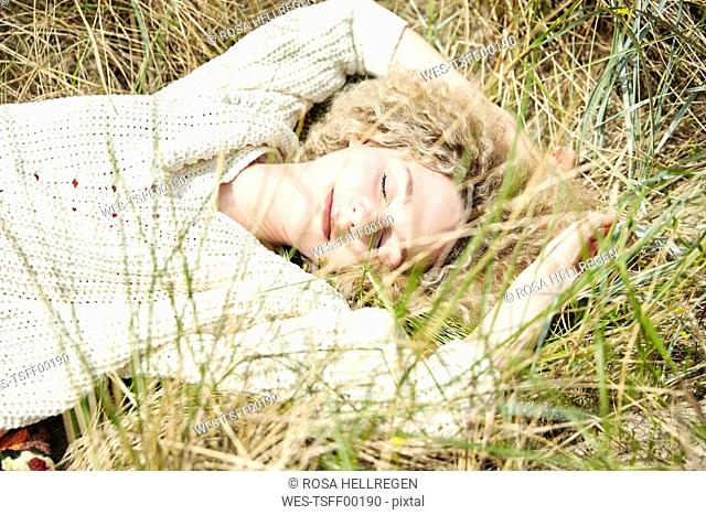 Portrait of smiling young woman with eyes closed relaxing in beach dunes