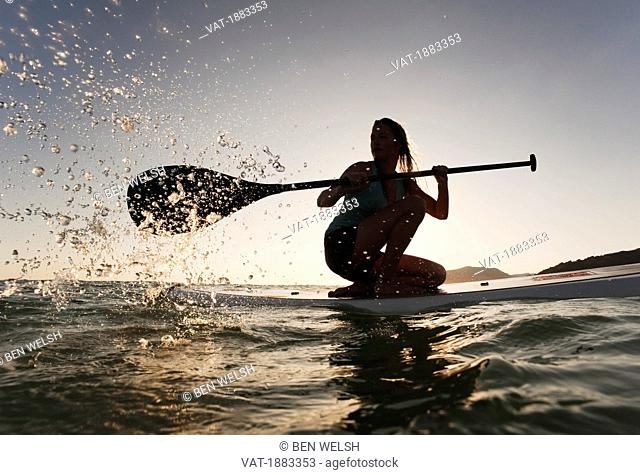 A Woman Paddling While On Her Knees On A Surf Board Off Dos Mares Beach, Tarifa, Cadiz, Andalusia, Spain