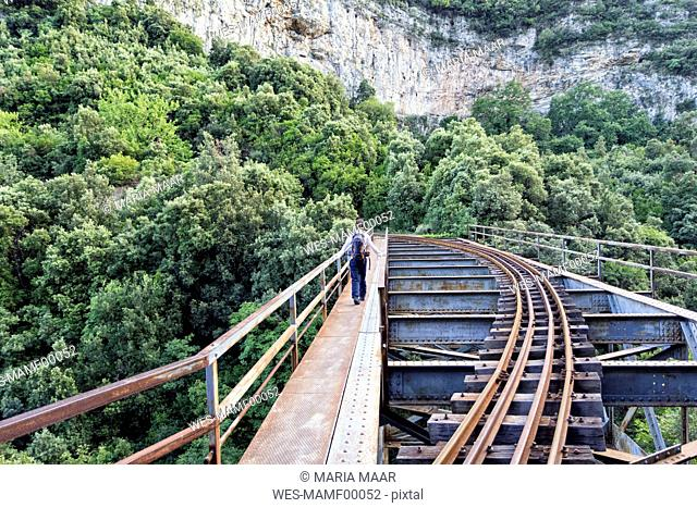 Greece, Pilion, Milies, back view of man walking on bridge along rails of Narrow Gauge Railway