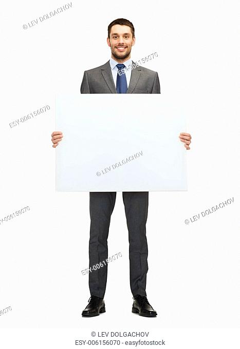 business, education, office and advertising concept - smiling businessman with big white blank board